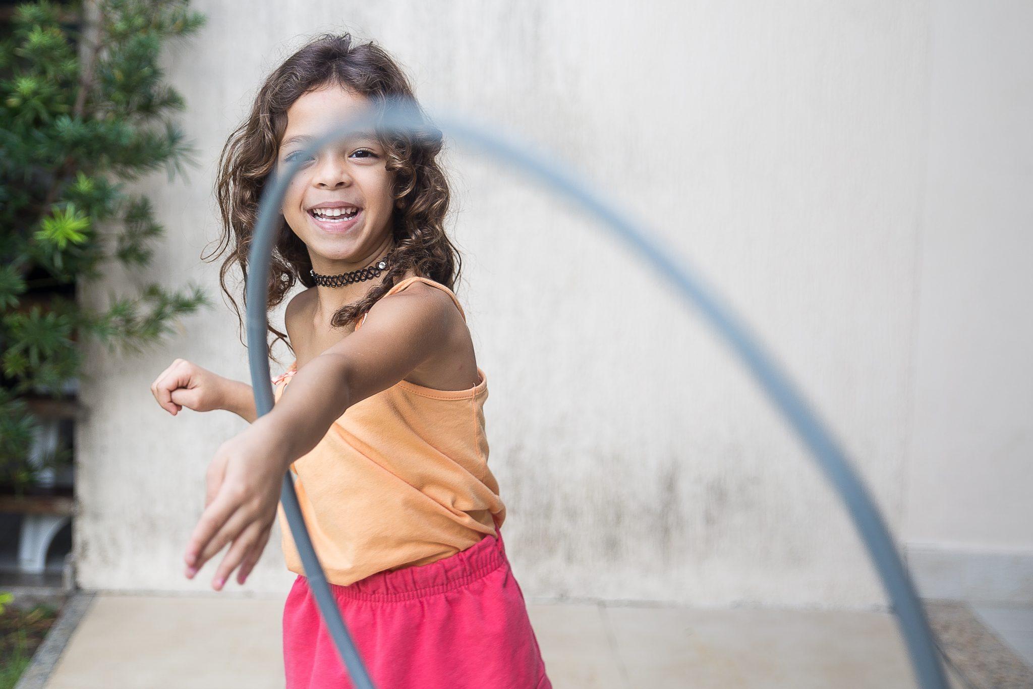 niña jugando hula-hoop en su brazo